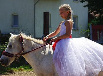 Model im Prinzessinnenkleid auf dem Rücken ihres Pferdes.